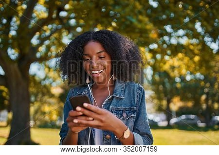 Portrait Of Smiling Young African American Woman Listening To Music On Earphone Using Mobile Phone I