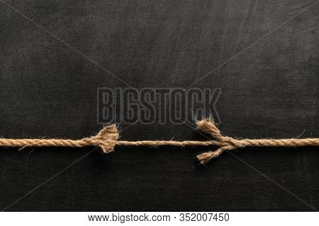 Long, Old Frayed Rope Is Breaking Off. Isolated On Black