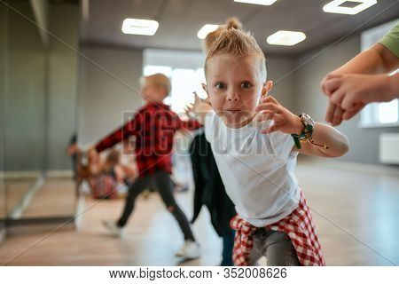 Full Of Energy. Cute Little Boy In White T-shirt Looking At Camera And Gesturing While Having A Chor