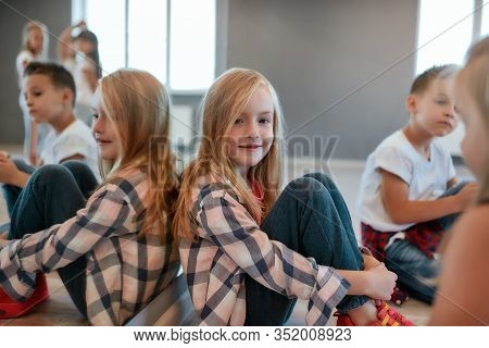 Portrait Of Happy Cute Little Girl In Checkered Shirt Looking At Camera And Smiling While Having A C