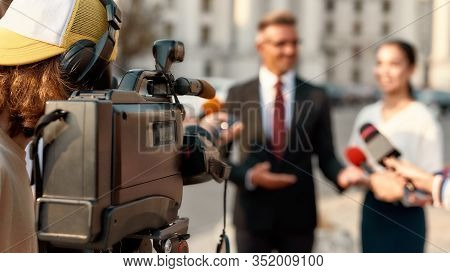 Horizontal Shot Of Video Camera Operator Recording Interview Of Politician. People Making Interview