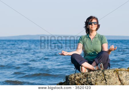 Young Woman Meditating On The Beach