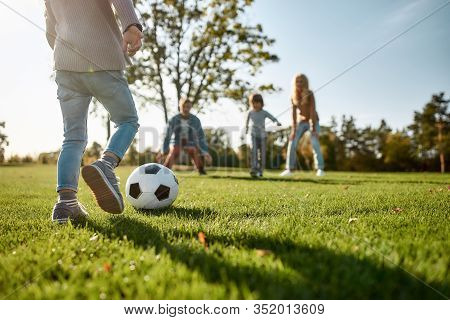 Cropped Portrait Of Cheerful Little Girl Playing Football With Her Family In The Park On A Sunny Day