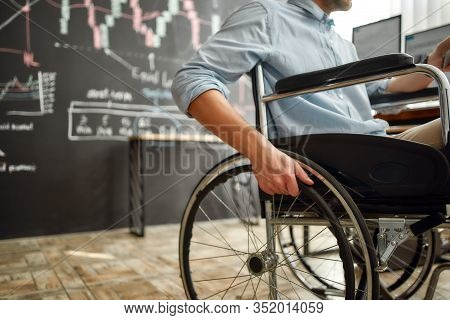 Cropped Photo Of Male Office Worker In A Wheelchair Working In The Modern Office. Disabled Man Holdi