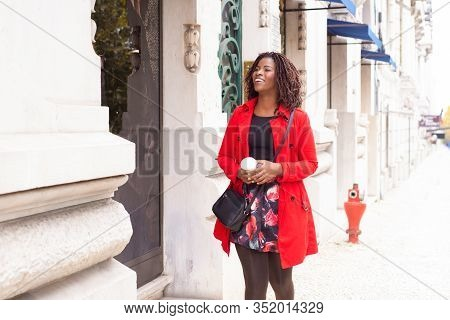 Smiling African American Woman Strolling On City Street. Beautiful Young Lady Holding Paper Cup Of C