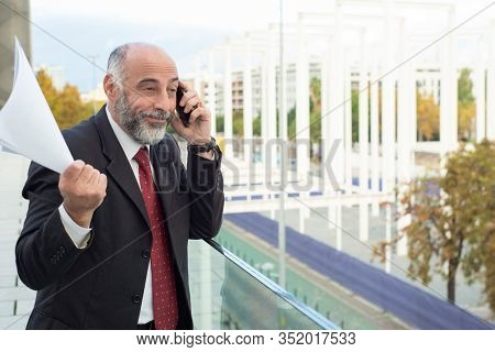 Disappointed Mature Man Talking On Phone. Grieved Bearded Businessman Holding Paper Documents In Rai