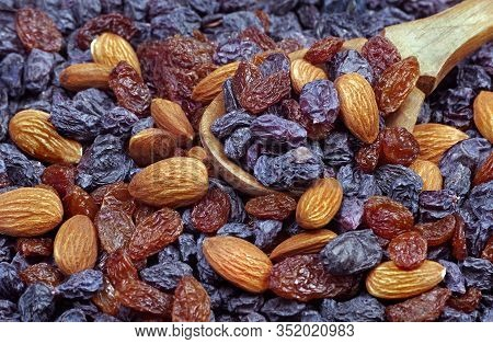 Sweet Dry Fruits And Nuts. Raisins And Almonds Texture Background. Raisins And Nuts In A Wooden Spoo