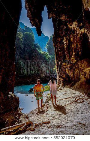 Hidden Beach With Huge Cave Near Koh Poda Island Krabi Thailand, Men At A Limestone Cliff Looking Ou