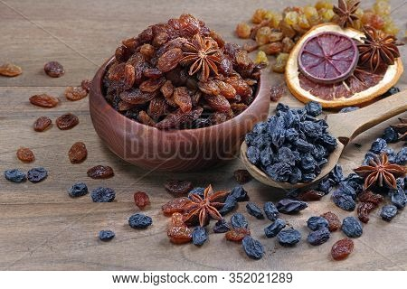 Red Raisins In A Bowl On A Wooden Table.  Black Raisins In A Spoon. Different Varieties Of Raisins A