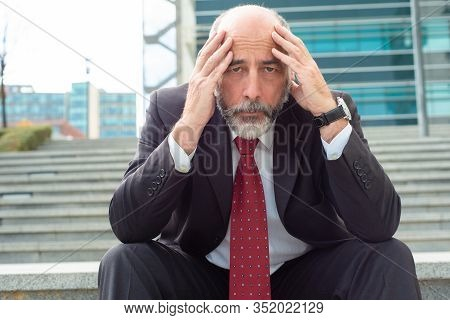 Front View Of Depressed Mature Businessman. Upset Middle Aged Worker Holding Hands On Head And Looki