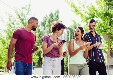 Happy Joyful Friends With Smartphones Discussing Funny News. Men And Women Walking Together Outside,