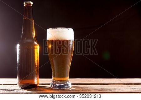 Cold Tasty Beer On A Hot Summer Day. Beer Glass And Bottle On Dark Table And Wall Background