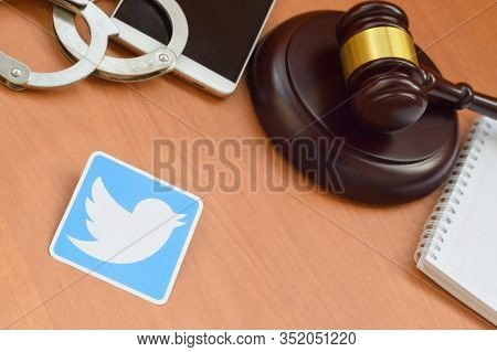 Twitter Paper Logo Lies With Wooden Judge Gavel, Smartphone And Handcuffs. Entertainment Lawsuit Con