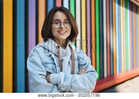 Cheerful Young Queer Girl In Glasses, Denim Jacket, Standing Near Rainbow Wall, Cross Hands Over Che