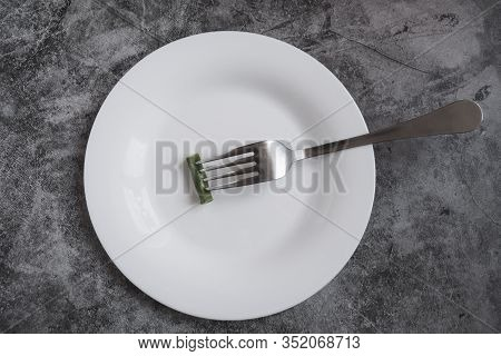 Empty White Plate With Some Food And A Metal Fork On A Gray Background. The Concept Of Anorexia, Wei