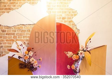 Photozone: Wooden Arch Painted In Warm Colors With Flowers On Brick Wall Background