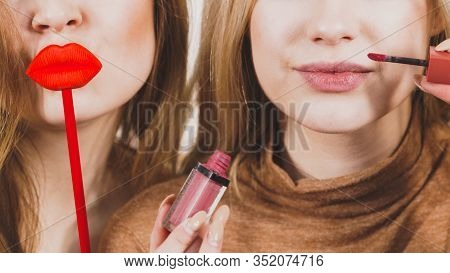 Two Women Having Fun While Doing Make Up. Friends Holding Lip Gloss Or Lipstick And Fake Lips On Sti