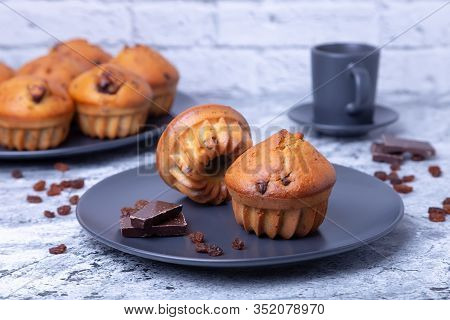 Muffins With Chocolate And Raisins. Homemade Baking. In The Background Is A Plate With Muffins And A