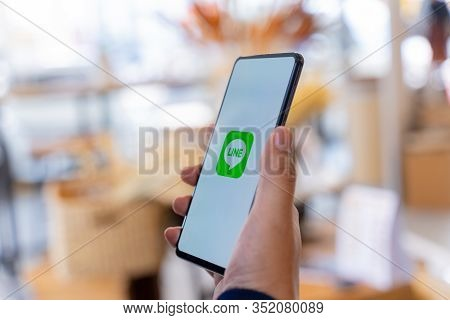 Chiang Mai, Thailand - Jan.18,2020: Man Holding Xiaomi Mi Mix 3 With Line Apps On Screen On Wood Des