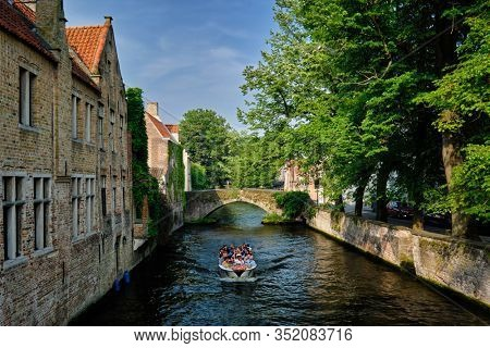 BRUGES, BELGIUM - MAY 28, 2018: Tourist boat with tourists in canal between old houses. Brugge Bruges, Belgium
