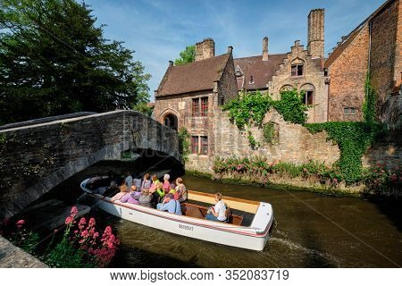 BRUGES, BELGIUM - MAY 28, 2018: Tourist boat with tourists passing under Bonifacius Bridge and medieaval houses in Bruges, Belgium
