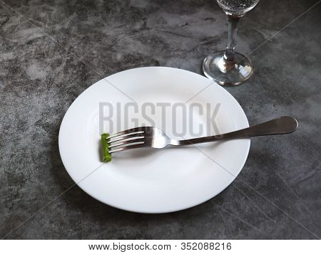 Empty White Plate With Small Peas And A Metal Fork On A Gray Background. A Glass Of Water In The Bac