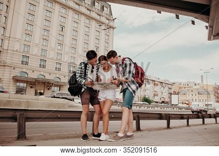 A Team Of Friends Look At The Map Of The City. Three Young Students Are Looking On The Map Of The Ci