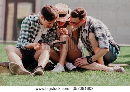 The Youngsters Leaned Together Over A Mobile Choosing The Best Photo Sitting On The Grass On A Summe