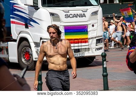 Malmö, Sweden - July 20, 2019: A Bare Chested Man Is Walking In Front Of A Scania Truck As They Both