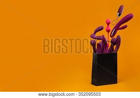 A paper shopping bag filled with Purple silicone sex toys on a yellow background. Erotic toy for fun. Sex gadget and masturbation device. View from above. Place for text. Flat lay. Sex shop concept.
