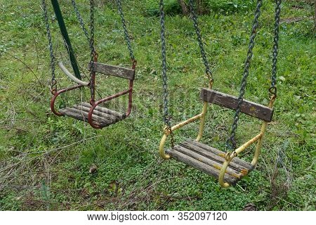 Vintage Wooden Swing Seats In Disused Playground.