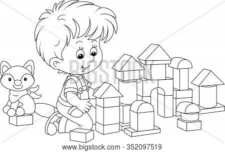 Little Boy Smiling, Playing With Bricks And Constructing A Toy Fortress For A Game, Black And White