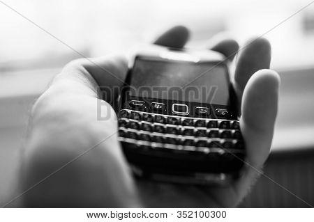 London, United Kingdom - Apr 21, 2013: Man Hand Holding Tilt-shift Lens Used On Blackberry Palm Vint