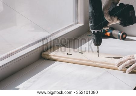 A Man Holds A Cordless Screwdriver In His Hand And Wraps The Screw In A Board.