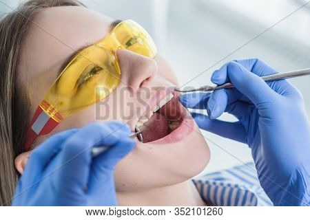A Dentist Examines A Patient, Close-up Of A Patient With An Open Mouth Next To Which Dental Objects