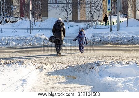 A Woman With A Child Crosses The Road Unsafe In Winter