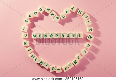 menopause word written on square block surroungd by heart shape. menopause text on orange background