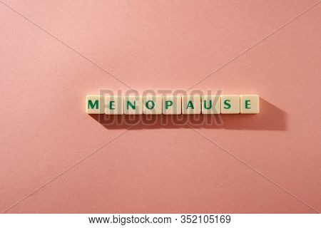 menopause word written on square block. menopause text on orange background