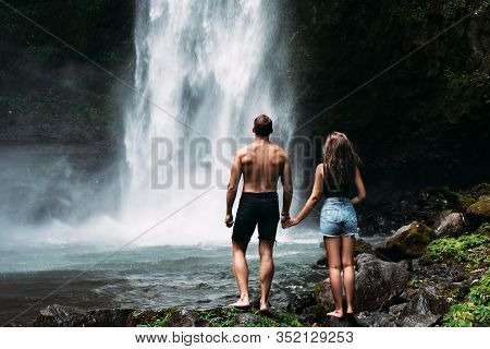 Lovers At The Waterfall, Rear View. Couple Admiring A Beautiful Waterfall In Indonesia. Couple On Va