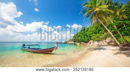 Tropical beach with coconut palm and longtail boat