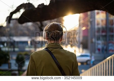 Woman With Headphones In City Street Sunset. Woman City Life Lifestyle. City People. Busy People Lif