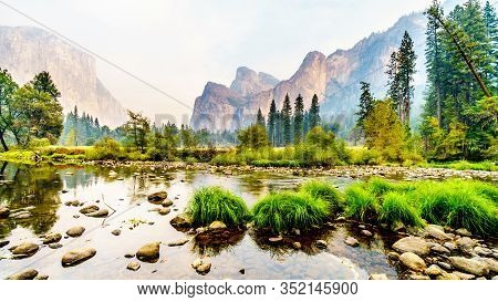 Reflections Of Cathedral Rocks, Taft Point And Sentinel Dome In The Merced River In The Smoke Filled