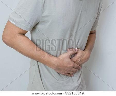 Man Suffering From Stomach Ache With Both Palm Around Waistline To Show Pain And Injury On Belly Are