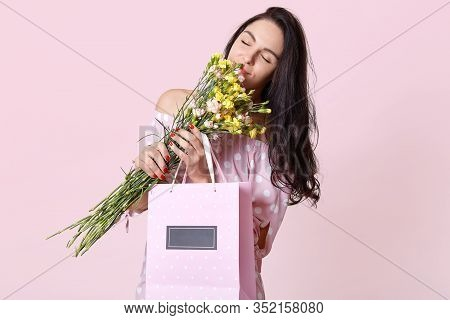 Indoor Shot Of Charming, Beautiful Girl Wearing Pink Sundress Holding Cute Bouquet Of Flowers. Lady