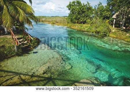 Sunny Seven Colored Lagoon Surrounded By Tropical Plants In Bacalar, Quintana Roo, Mexico