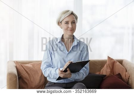 Professional Psychotherapy. Successful Psychologist Holding Folder Smiling To Camera Sitting On Sofa