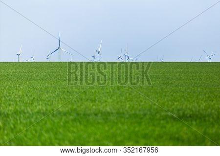 Alternative Wind Energy. Wind Turbines Generating Electricity On Sunny Field