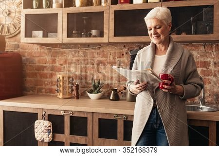Smiling Elderly Lady Drinking Morning Coffee And Reading Fresh Newspaper At Kitchen, Enjoying Retire