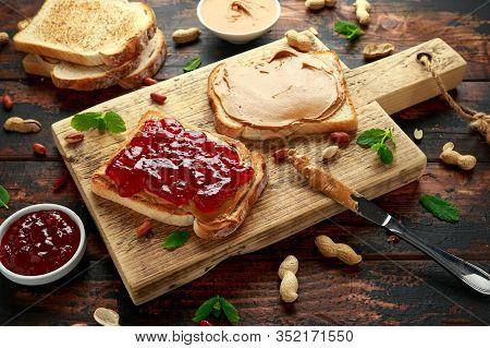Peanut Butter And Strawberry Jelly Sandwich On Wooden Board. Morning Breakfast