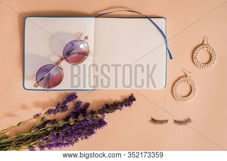 Womens Accessories. Natural Eco Straw Bag, Bamboo Earrings, Eyelashes For Women On A Pink Background